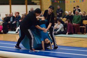 Barn bliver hjulpet til en salto